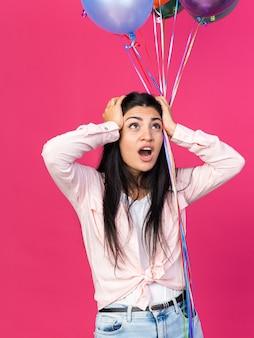 Bang kijkend naar jong mooi meisje met ballonnen greep het hoofd