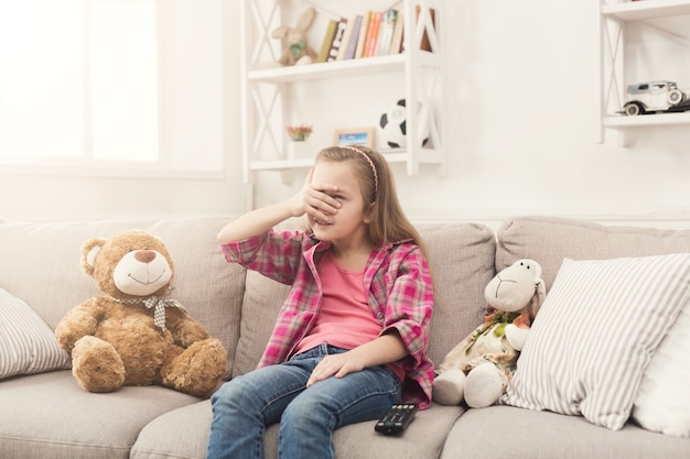Bang klein casual meisje tv kijken. bang vrouwelijk kind zittend op de bank met gesloten ogen, alleen thuis, kijken naar verboden enge films met haar speelgoedvrienden teddybeer en schapen, kopieer ruimte