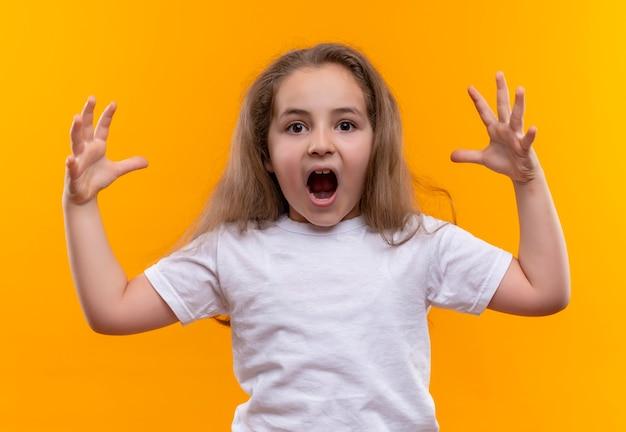 Bang klein schoolmeisje dat een wit t-shirt draagt spreidt handen uit op geïsoleerde oranje achtergrond