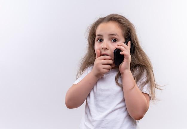 Bang klein schoolmeisje dat wit t-shirt draagt spreekt over telefoon behandelde mond op geïsoleerde witte achtergrond