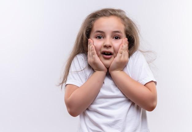Bang klein schoolmeisje met een wit t-shirt legde haar handen op de wangen op afgelegen witte achtergrond