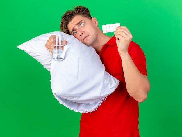Bang knappe blonde zieke jongeman met kussen hoofd erop houden glas water en pack van medische tabletten kijken camera geïsoleerd op groene achtergrond
