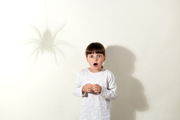 Bang meisje met een wit casual shirt dat weer poseert op de grijze muur met schaduw van spin, vrouwelijk kind met wijd geopende mond, bewegingloos staand, fobie voor insecten.