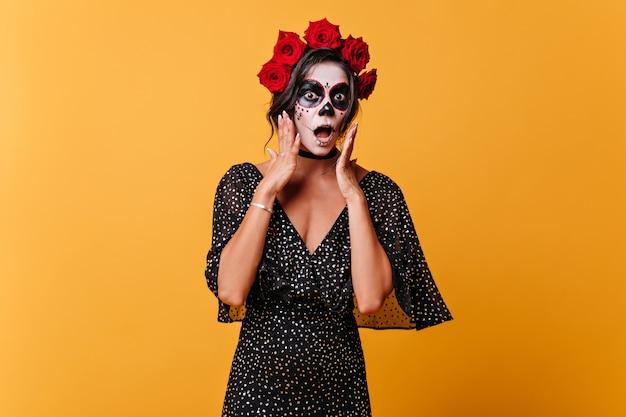 Bang meisje met halloween-masker opende van verbazing haar mond. portret van een vrouw in polka dot jurk op geïsoleerde muur.
