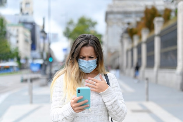 Bang meisje met masker leest nieuws op haar telefoon over straatziekte