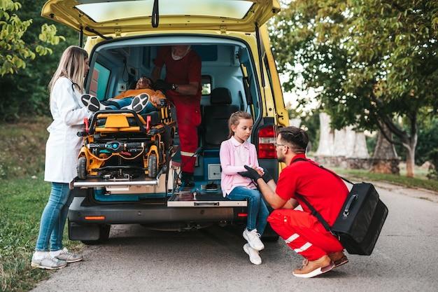Bang meisje staat naast haar gewonde moeder en artsen.