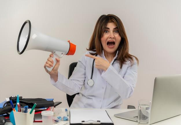 Bang middelbare leeftijd vrouwelijke arts dragen medische gewaad met stethoscoop zittend aan bureau werken op laptop met medische hulpmiddelen houden en wijst naar luidspreker op witte muur
