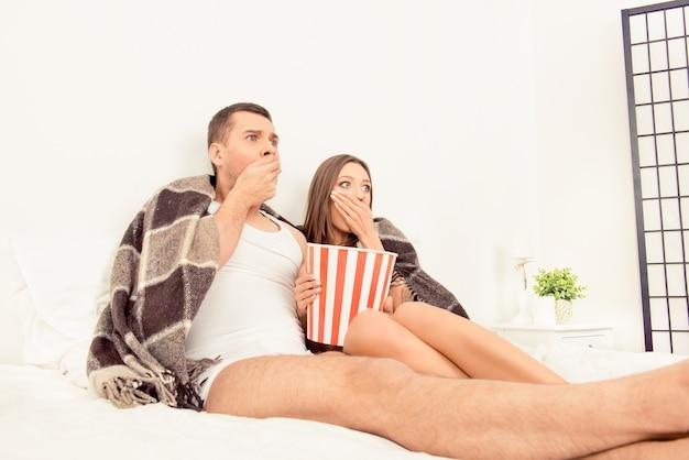 Bang mooi jong koppel thuis kijken naar een film en eten popcorn