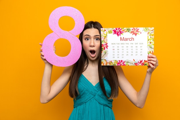 Bang mooi jong meisje op gelukkige vrouwendag met kalender met nummer acht rond gezicht geïsoleerd op oranje muur