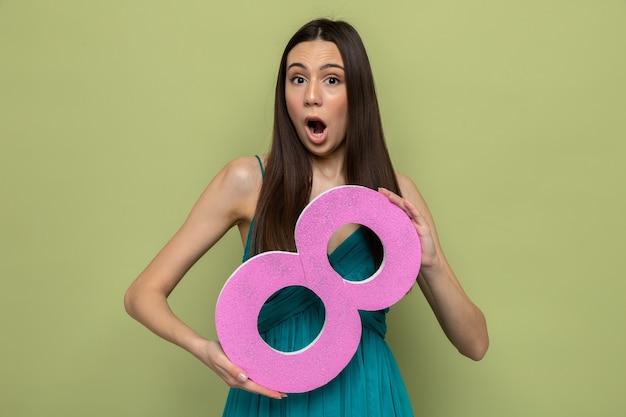 Bang mooi jong meisje op gelukkige vrouwendag met nummer acht geïsoleerd op olijfgroene muur