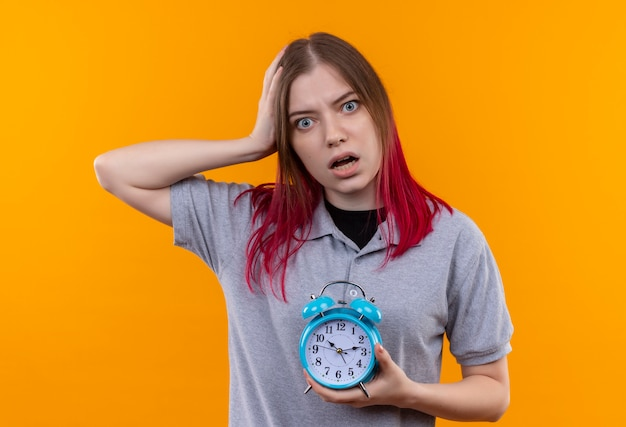 Bang mooi meisje dragen grijze t-shirt bedrijf wekker hand op het hoofd zetten geïsoleerde gele achtergrond