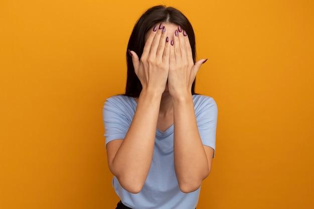 Bang mooie brunette vrouw behandelt gezicht met handen geïsoleerd op een oranje muur