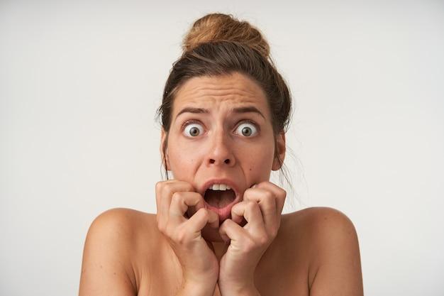 Bang mooie jonge vrouw hand in hand op het gezicht, bang op zoek met grote ogen en mond geopend, zonder make-up