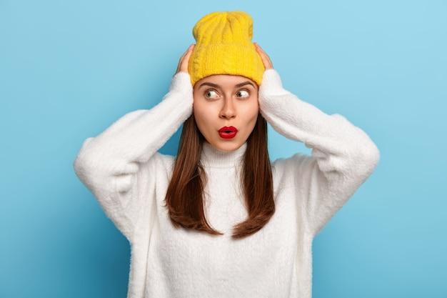 Bang mooie jonge vrouw houdt beide handen op het hoofd, kijkt opzij met angst, heeft lang donker haar, draagt gele hoofddeksels en witte zachte trui, gefocust opzij, geïsoleerd op blauwe achtergrond