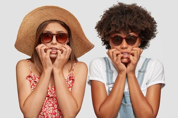 Bang nerveus diverse vrouwen bijten nerveus vingernagels, kijken wanhopig naar de camera, staan naast elkaar