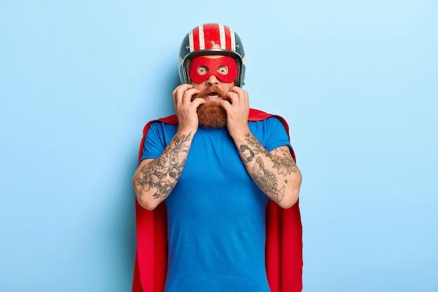 Bang nerveuze man kijkt met angst, draagt helm, rood masker en mantel, bereidt zich voor op de vlucht