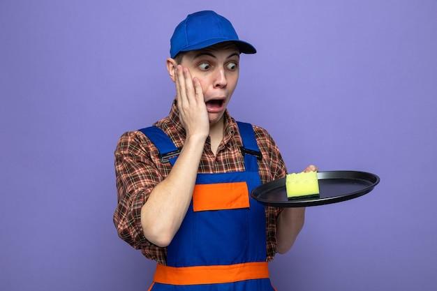 Bang om de hand op de wang te leggen, jonge schoonmaakster die een uniform draagt en een pet vasthoudt en naar de spons op het dienblad kijkt