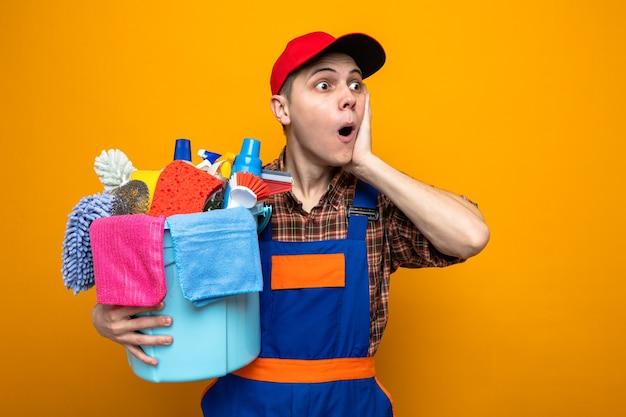 Bang om de hand op de wang te leggen, jonge schoonmaakster met uniform en pet met emmer met schoonmaakgereedschap