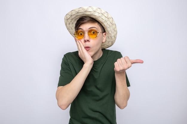 Bang om de hand op de wangen te leggen aan de zijkant van een jonge knappe kerel met een hoed met een bril Premium Foto