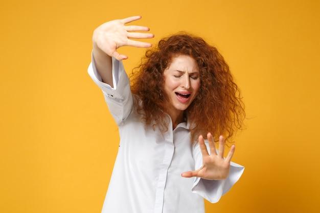 Bang ontevreden jonge roodharige vrouw meisje in casual wit overhemd poseren geïsoleerd op geel oranje muur