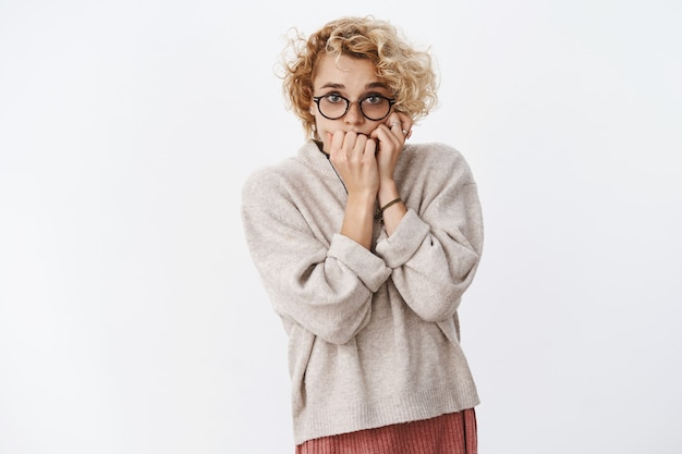 Bang onzekere en timide schattige blonde vrouw met kort kapsel in glazen hand in hand voor mond, bijtende vingernagels bang en doodsbang over witte muur kijken.