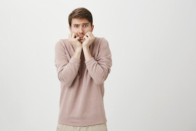 Bang, onzekere jongeman die geschrokken kijkt, bijtende nagels bang