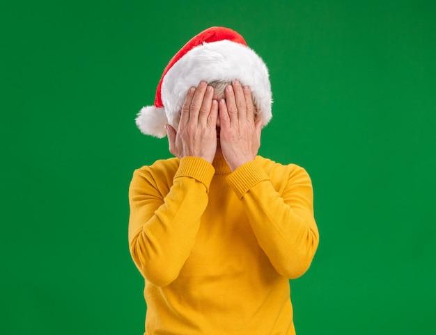Bang oudere vrouw met kerstmuts die gezicht bedekt met handen geïsoleerd op paarse achtergrond met kopie ruimte