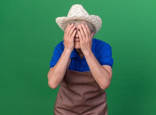 Bang oudere vrouwelijke tuinman tuinieren hoed dekt gezicht met handen op groen