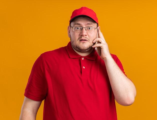 Bang overgewicht jonge bezorger in optische bril praten over telefoon geïsoleerd op oranje muur met kopie ruimte