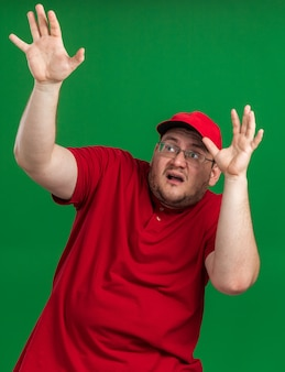 Bang overgewicht jonge bezorger in optische bril staat met opgeheven handen op zoek geïsoleerd op groene muur met kopieerruimte