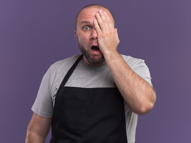 Bang slavische mannelijke kapper van middelbare leeftijd in uniform bedekt oog met hand geïsoleerd op paarse muur