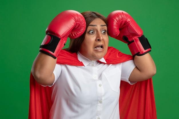 Bang superheld vrouwtje van middelbare leeftijd dragen bokshandschoenen hand in hand op het hoofd geïsoleerd op een groene achtergrond