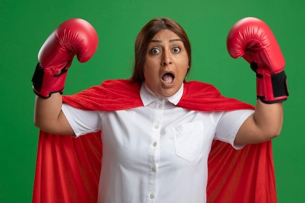 Bang superheldwijfje dat van middelbare leeftijd bokshandschoenen draagt die handen opheffen die op groen worden geïsoleerd