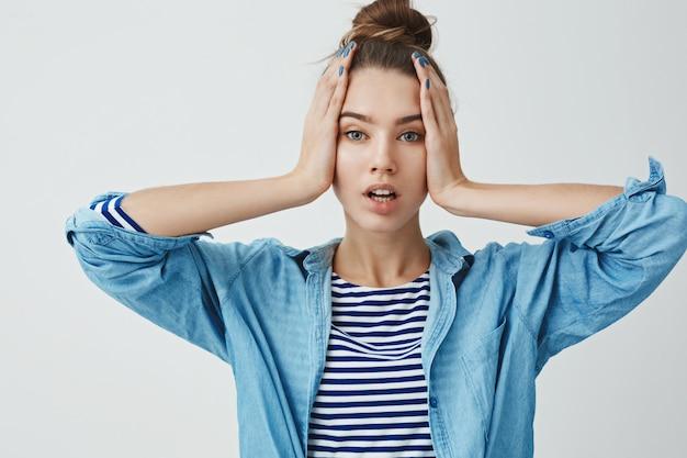 Bang tiener vrouw met handen op het hoofd