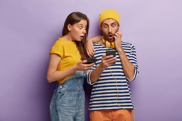 Bang tienerpaar kijkt iets op een mobiel, geschokt