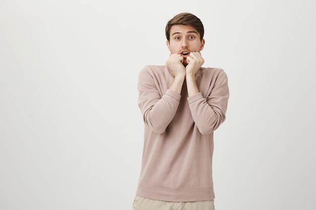 Bang timide jongeman op zoek bang met handen in de buurt van mond