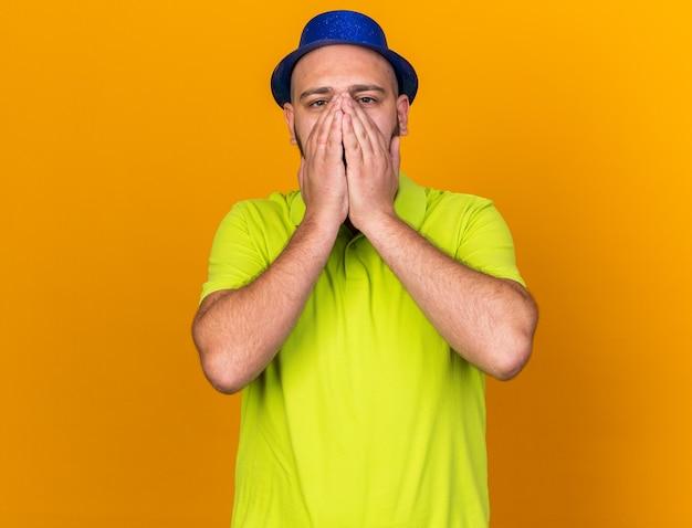 Bang uitziende camera jonge man met feestmuts bedekt gezicht met handen geïsoleerd op oranje muur