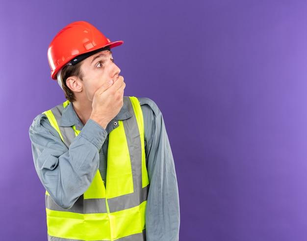 Bang uitziende jonge bouwvakker in uniform bedekte mond met hand