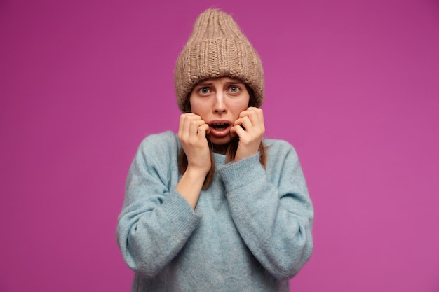 Bang uitziende vrouw, doodsbang meisje met donkerbruin haar. het dragen van blauwe trui en gebreide muts. haar gezicht aanraken in angst over de paarse muur