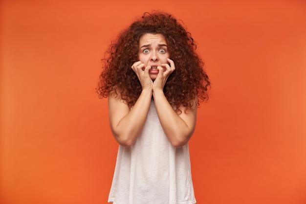 Bang uitziende vrouw, meisje met rood krullend haar. witte off-shoulder blouse dragen. haar gezicht aanraken. heeft angst op haar gezicht. geschokt, geïsoleerd over oranje muur
