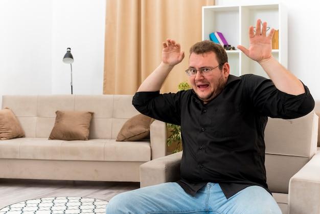Bang volwassen slavische man in optische bril zit op fauteuil met opgeheven handen in de woonkamer