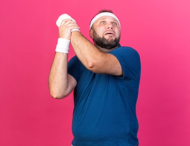 Bang volwassen slavische sportieve man met hoofdband en polsbandjes die zijn hand vasthouden en omhoog kijken geïsoleerd op roze muur met kopie ruimte