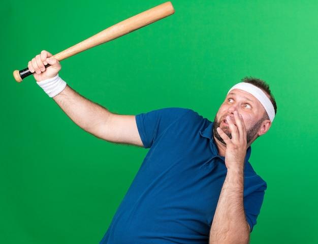 Bang volwassen slavische sportieve man met hoofdband en polsbandjes houden en kijken naar vleermuis geïsoleerd op groene muur met kopie ruimte