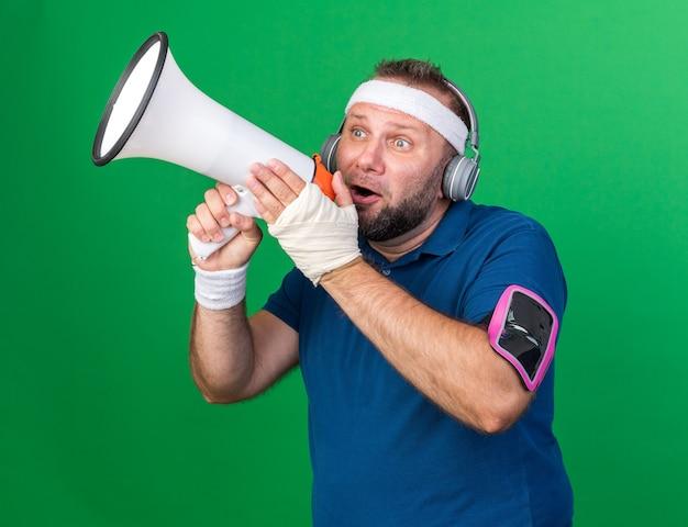 Bang volwassen slavische sportieve man op koptelefoon dragen hoofdband polsbandjes en telefoon armband spreken in luidspreker geïsoleerd op groene muur met kopie ruimte