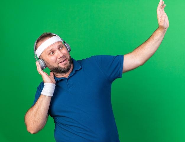 Bang volwassen slavische sportieve man op koptelefoon met hoofdband en polsbandjes kijkend naar de zijkant die hand omhoog steekt geïsoleerd op groene muur met kopieerruimte