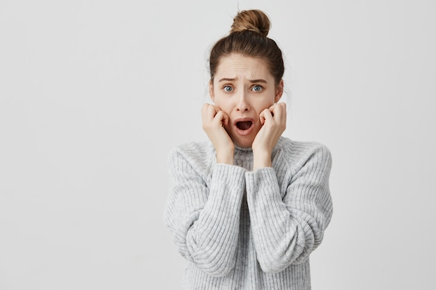 Bang vrouw in grijze trui met haar hand op de wangen met geopende mond doodsbang. vrouwelijke grafisch ontwerper die zich zorgen maakt over het missen van de deadline. overtreding concept