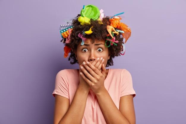 Bang vrouw met donkere huid bedekt de mond met beide handen, heeft problemen met het verbeteren van de omgeving, is in paniek, draagt een t-shirt, geïsoleerd over een paarse muur. vervuiling en milieubewustzijn verminderen