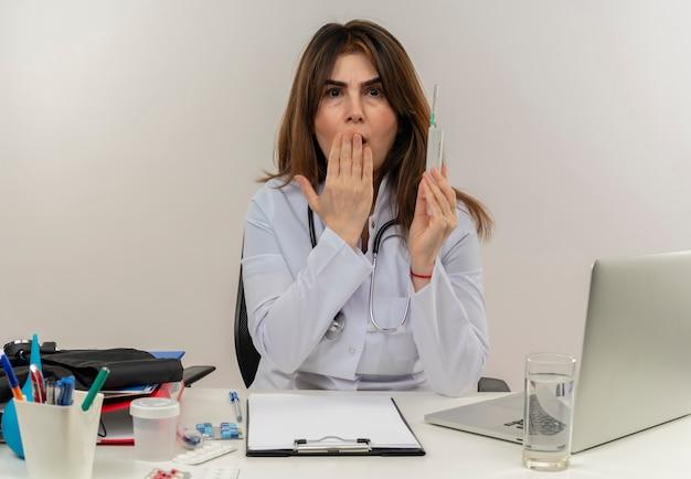 Bang vrouwelijke arts van middelbare leeftijd die het dragen van medische mantel met stethoscoop zittend aan bureau werkt op laptop met medische hulpmiddelen houdt spuit bedekt mond met hand op geïsoleerde witte muur