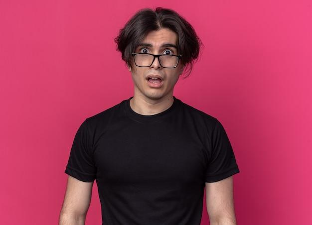 Bang wild haar jonge knappe kerel met zwarte t-shirt en bril geïsoleerd op roze muur