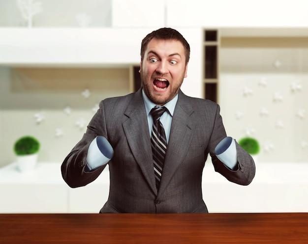 Bang zakenman zonder armen zit aan tafel